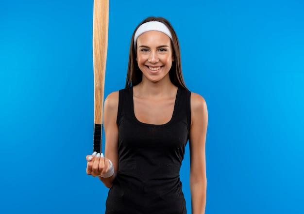 Sonriente joven bastante deportivo vistiendo diadema y muñequera sosteniendo un bate de béisbol aislado en el espacio azul