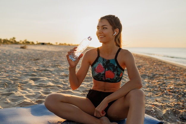 Sonriente joven bebiendo agua dulce y escuchando música en auriculares después del entrenamiento. mujer atlética joven que ejercita cerca del mar. puesta de sol de verano.