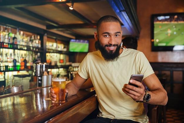 Sonriente joven bebiendo cerveza y usando un teléfono celular en el pub
