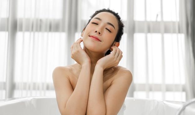 Sonriente de joven bella mujer asiática limpia piel blanca sana fresca tocando su cara con la mano y aplicando crema en casa.