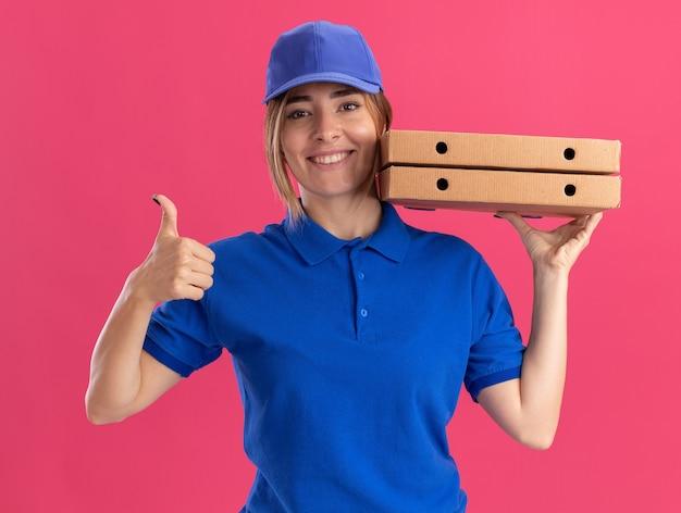 Sonriente joven bonita repartidora en uniforme pulgar hacia arriba y sostiene cajas de pizza cerca de la cara en rosa