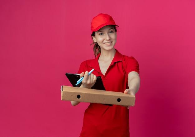 Sonriente joven bonita repartidora en uniforme rojo y gorra estirando el paquete de pizza en la cámara y sosteniendo la pluma con el portapapeles aislado sobre fondo carmesí con espacio de copia