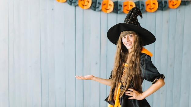 Sonriente joven bruja mostrando disfraz de halloween