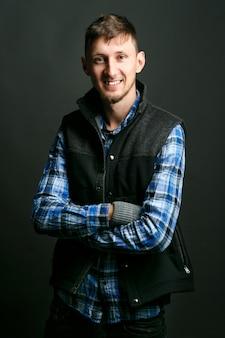 Sonriente joven en camisa azul y chaleco oscuro