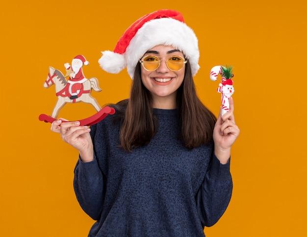Sonriente joven caucásica en gafas de sol con sombrero de santa sostiene a santa en la decoración del caballo mecedora y bastón de caramelo aislado en la pared naranja con espacio de copia