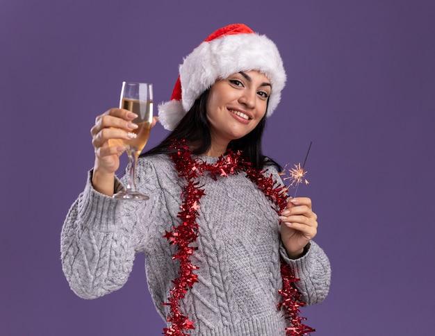 Sonriente joven caucásica con sombrero de navidad y guirnalda de oropel alrededor del cuello sosteniendo bengala de vacaciones y copa de champán mirando a cámara aislada sobre fondo púrpura