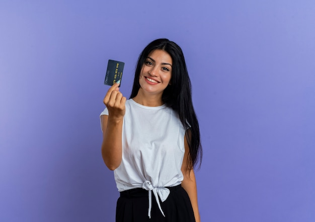 Sonriente joven caucásica tiene tarjeta de crédito