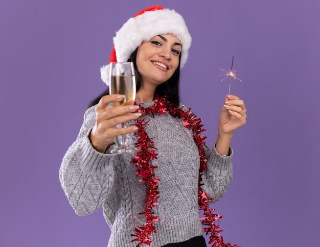 Sonriente joven caucásica vistiendo gorro de navidad y guirnalda de oropel alrededor del cuello sosteniendo bengala de vacaciones y extendiendo una copa de champán hacia aislados en la pared púrpura