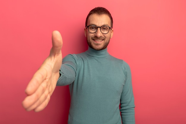 Sonriente joven caucásico con gafas haciendo gesto de saludo aislado en la pared carmesí con espacio de copia