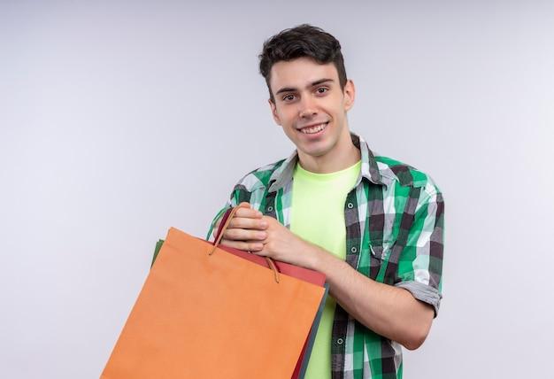 Sonriente joven caucásico vistiendo camisa verde sosteniendo bolsas de papel sobre fondo blanco aislado