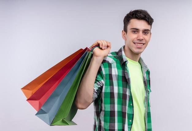 Sonriente joven caucásico vistiendo camisa verde sosteniendo bolsas de papel en su hombro sobre fondo blanco aislado