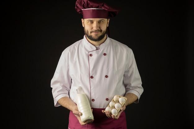 Sonriente joven chef masculino barbudo en uniforme sosteniendo una botella de plástico de leche y media docena de huevos