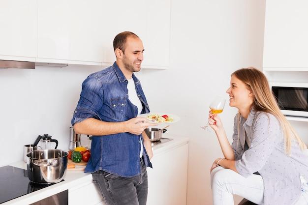Sonriente joven comiendo ensalada y su esposa bebiendo alcohol