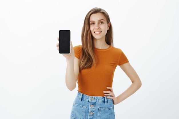 Sonriente joven confiada dar consejos, mostrando la pantalla del teléfono inteligente, demostrar la aplicación o comprar