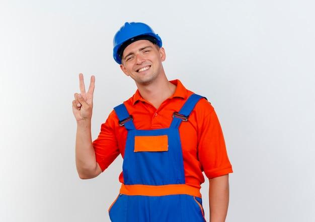 Sonriente joven constructor con uniforme y casco de seguridad mostrando gesto de paz en blanco