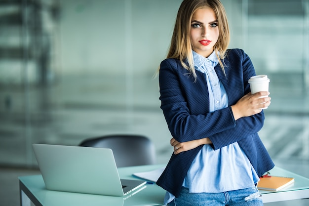 Sonriente joven dama de negocios confiada con el pelo rizado de pie en el escritorio común y mirando mientras bebe café en la oficina de espacios abiertos