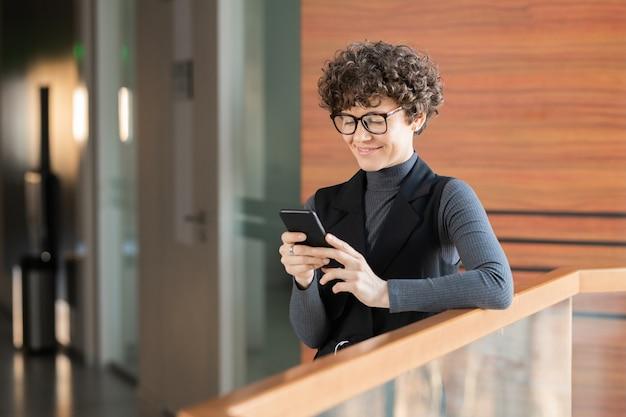 Sonriente joven dama de pelo rizado de pie en el pasillo y comprobando las estadísticas de las redes sociales en el teléfono