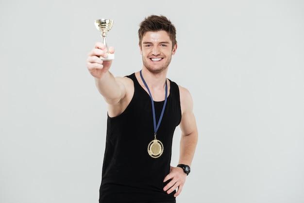 Sonriente joven deportista con recompensa