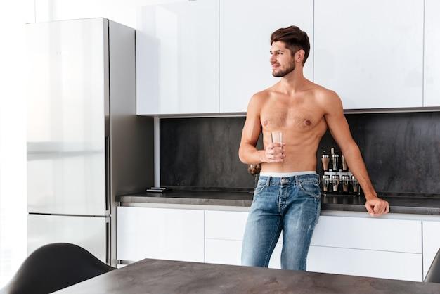 Sonriente joven descamisado de pie y bebiendo agua en la cocina