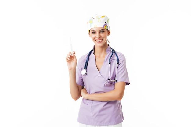 Sonriente joven doctora en uniforme con fonendoscopio en el cuello sosteniendo la jeringa en la mano felizmente