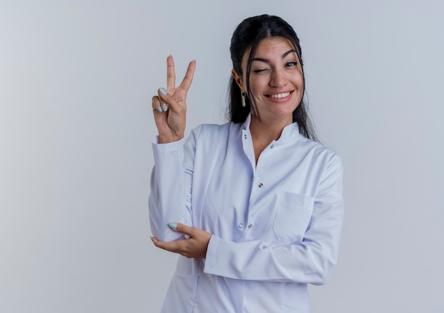 Sonriente joven doctora vistiendo bata médica haciendo el signo de la paz poniendo la mano en el codo aislado en la pared blanca con espacio de copia