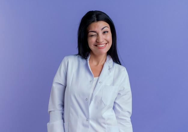 Sonriente joven doctora vistiendo bata médica mirando y guiñando un ojo