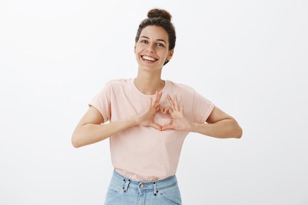Sonriente joven elegante posando contra la pared blanca