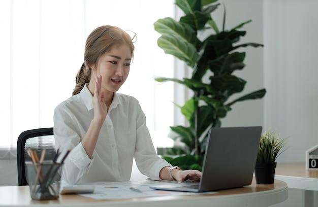 Sonriente a joven empleada en casa onda de mano en videollamada en portátil con diversos colegas. la trabajadora asiática tiene una conferencia por cámara web o una reunión del equipo web digital o una sesión informativa con sus compañeros de trabajo.