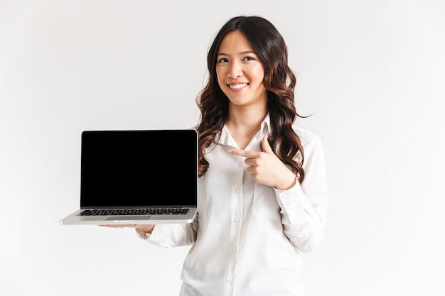 Sonriente joven empresaria asiática apuntando