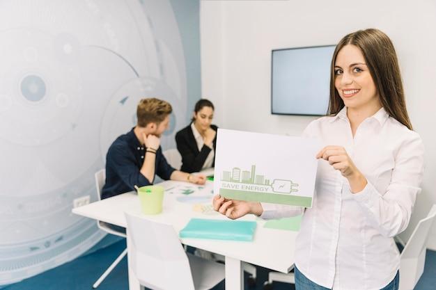 Sonriente joven empresaria mostrando el concepto de ahorro de energía en la oficina