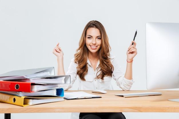 Sonriente joven empresaria sosteniendo la pluma mientras está sentado en el escritorio de oficina sobre fondo blanco.