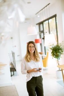 Sonriente joven empresaria mediante teléfono móvil en la oficina moderna