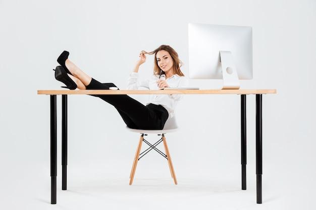 Sonriente joven empresaria usando laptop y escribiendo con las piernas sobre el escritorio sobre fondo blanco.