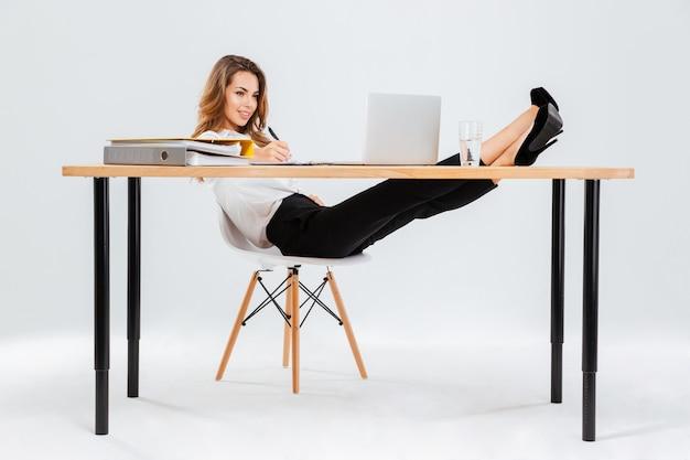 Sonriente joven empresaria usando laptop y escribiendo con las piernas sobre la mesa sobre fondo blanco.