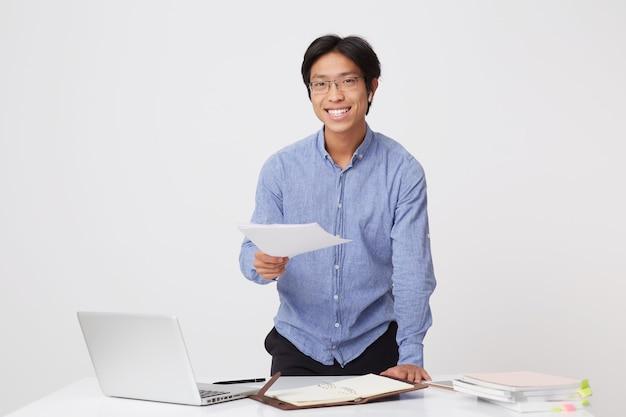 Sonriente joven empresario asiático en gafas y camisa azul con auriculares trabajando con ordenador portátil y documentos en el lugar de trabajo de pie sobre la pared blanca