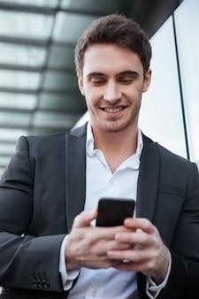 Sonriente joven empresario caminando cerca del centro de negocios charlando