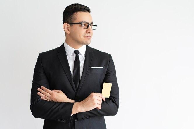 Sonriente joven empresario con propósito con tarjeta de crédito mirando a un lado.