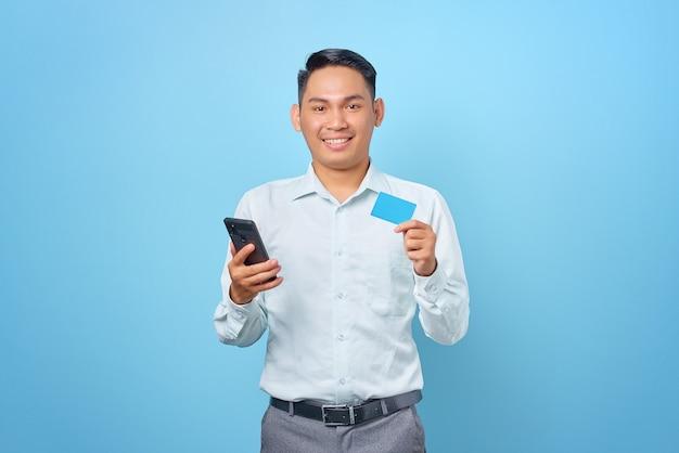 Sonriente joven empresario guapo sosteniendo smartphone y tarjeta de crédito sobre fondo azul.