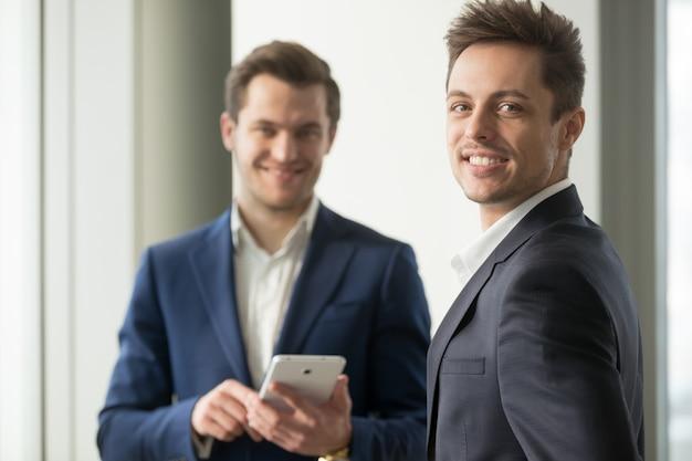 Sonriente joven empresario mirando a cámara, desarrollar aplicación
