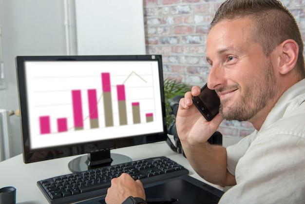 Sonriente joven empresario en la oficina hablando por teléfono