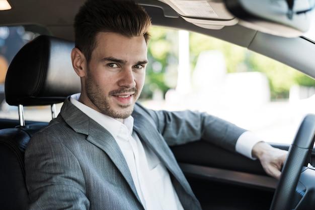 Sonriente joven empresario viaja en coche