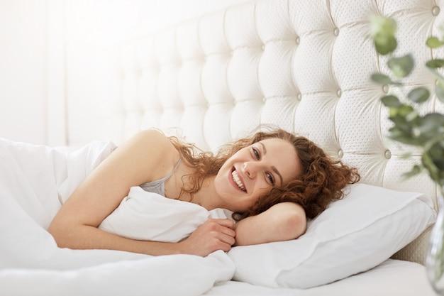 Sonriente joven encantadora se despierta en la mañana