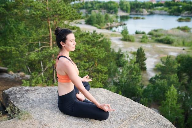 Sonriente joven enérgica con bus de pelo sentado con las piernas cruzadas sobre piedra durante la meditación al aire libre