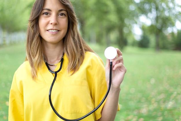 Sonriente joven enfermera con estetoscopio en mano