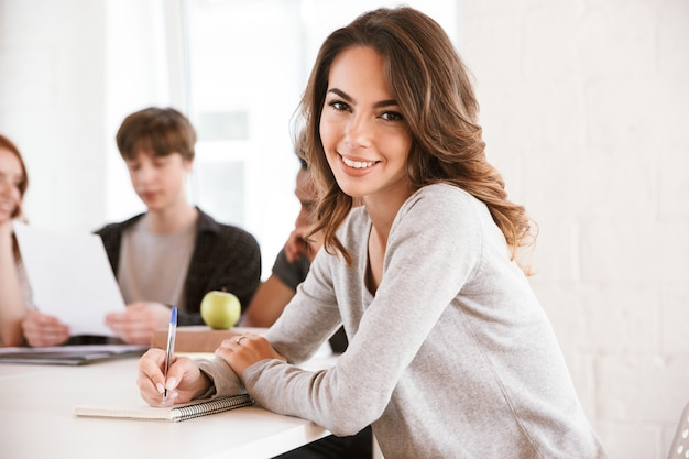 Sonriente joven escribiendo notas