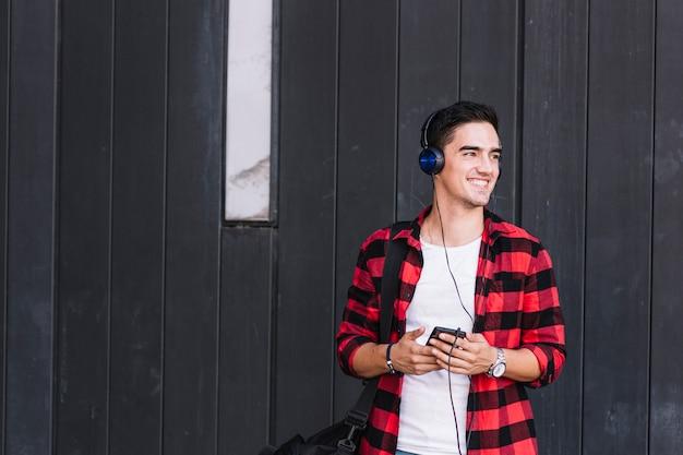 Sonriente joven escuchando música en frente de la pared de madera negra
