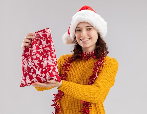 Sonriente joven eslava con gorro de papá noel y con guirnalda alrededor del cuello sostiene una bolsa de regalo de navidad aislada en la pared blanca con espacio de copia