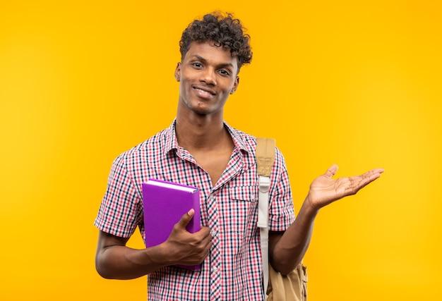 Sonriente joven estudiante afroamericano con mochila sosteniendo el libro y manteniendo la mano abierta