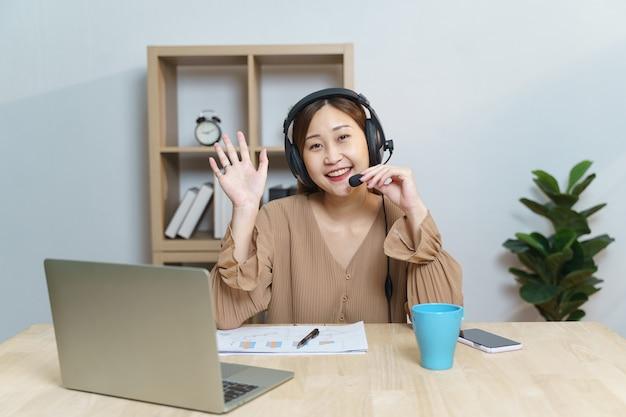 Sonriente joven estudiante asiática con auriculares escucha en la pantalla del portátil mientras habla y aprende cursos en línea. mujer de negocios china usa auriculares trabajando con videollamada para servicio al cliente