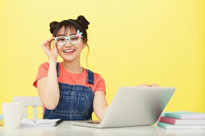 Sonriente joven estudiante asiática en gafas de colores brillantes, sentado en el escritorio con ordenador portátil